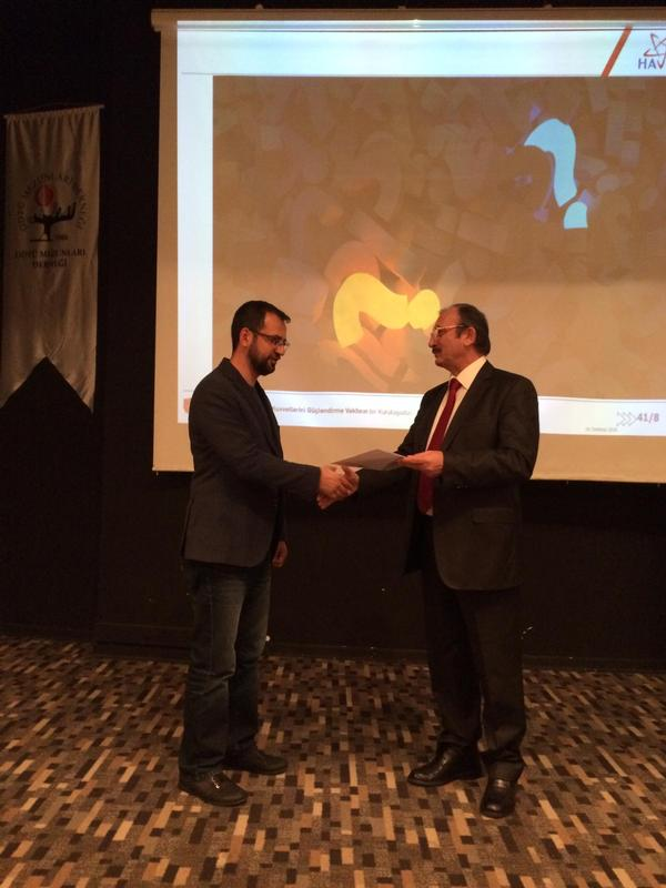 Chapter President Kamil Zafer Selçuk presents the certificate of appreciation to Turgut at the December meeting.